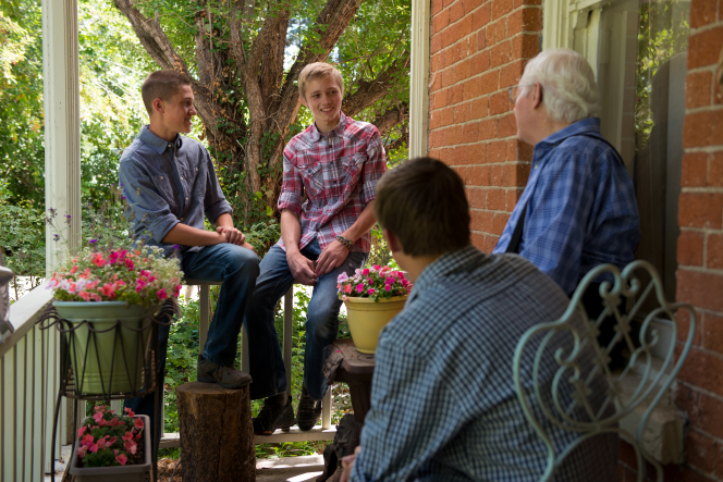 Two young men sitting on a porch railing and another sitting on a chair as they talk to an elderly man wearing a blue plaid shirt, suspenders, and glasses.