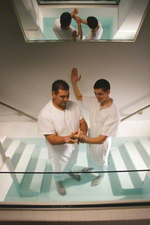 An elder missionary in white baptizes by raising his right arm and holding the wrist of another man in white in the baptismal font.