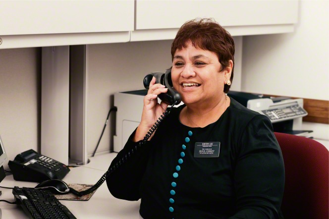 A senior sister missionary in a black long-sleeve shirt with blue buttons, talking on the phone at the LDS employment resource center.