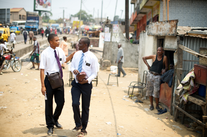 An elder missionary turning and putting his hand on his companion's shoulder while talking and walking down a dirt street in Africa.