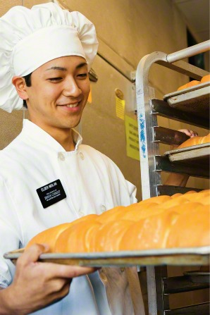 An elder missionary in a white apron and hat, serving in a bakery and carrying a pan with bread loaves.