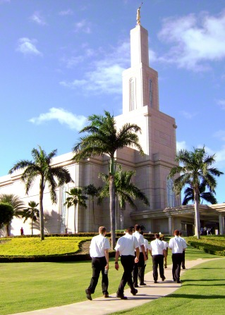 A group of elder missionaries in white shirts and black pants walking past palm trees toward the Santo Domingo Dominican Republic Temple.
