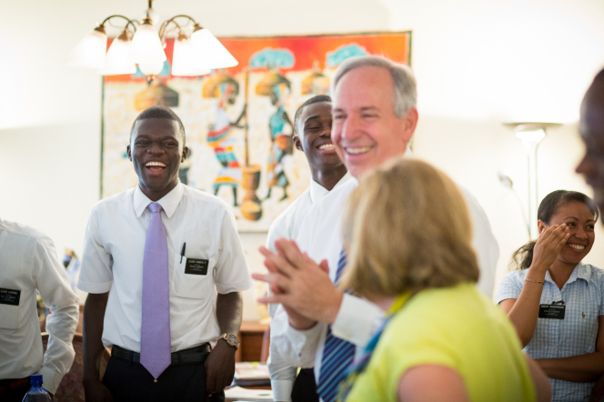 Elder and sister missionaries in Africa laugh while receiving training in a classroom from a senior missionary couple.