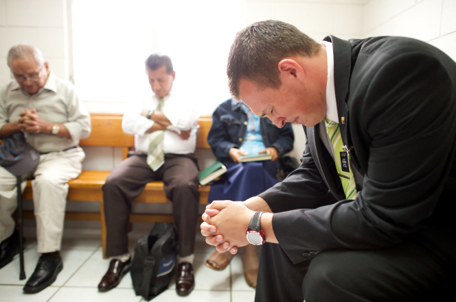 An elder missionary in Ecuador clasping his hands and praying with a group of men in a Church meeting.