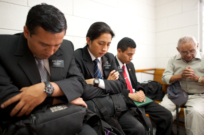 Three elder missionaries with black hair sitting beside each other and praying with a man in a Church meeting in Ecuador.