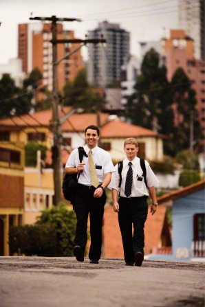 Two elder missionaries carrying backpacks and walking up a street in São Paulo, Brazil, with houses, trees, and tall buildings in the background.