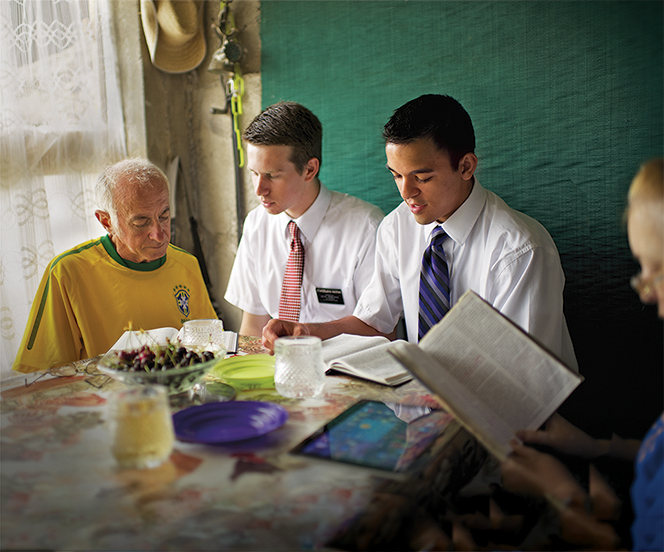 Two elder missionaries in Bulgaria sitting next to an elderly man in his home as they read scriptures together.