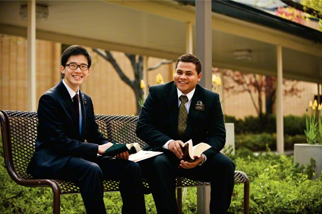 Two elder missionaries in white shirts, ties, and black suits sitting on a bench outside and reading scriptures at the Missionary Training Center.