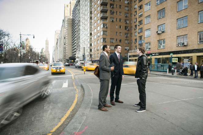 A young man in a black jacket talking to two elder missionaries in suits on a sidewalk near a busy street in New York City.