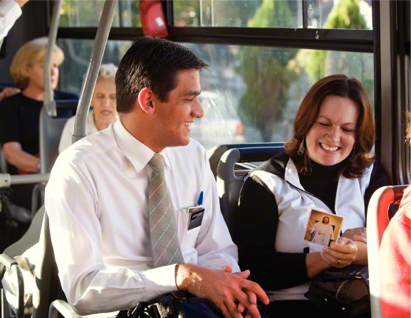 An elder missionary smiles while a woman sitting beside him on a bus in Brazil looks at a pass-along card with a picture of Christ.