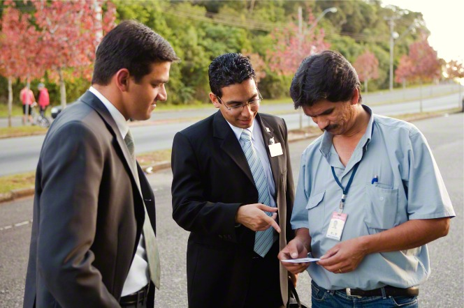 Two elder missionaries in suits standing and giving a pass-along card to a man in a blue shirt in Brazil.