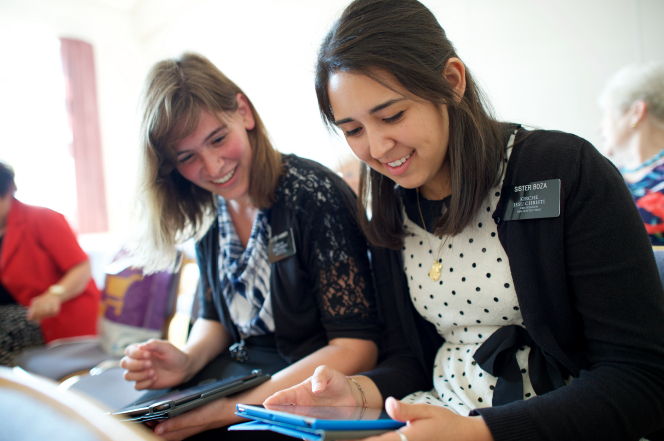 Two sister missionaries sit together inside a Church building and study on their tablets.