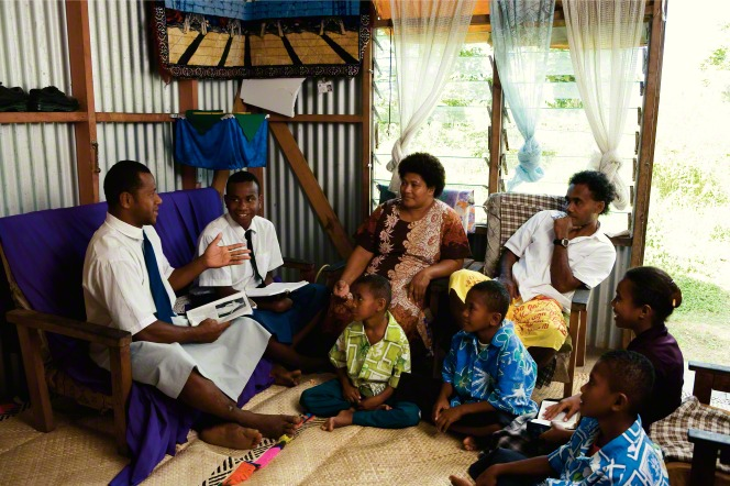 Two elder missionaries sit on a blue couch and teach a father, mother, and four children, who are sitting on chairs and the floor in their home in Tonga.