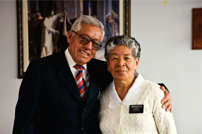 A senior elder missionary wearing glasses puts his arm around his wife's shoulders as they stand in front of a painting of Christ in Mexico City.