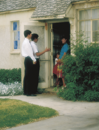 Two elder missionaries standing outside a home, talking to a woman in a blue shirt and her daughter in a red dress.