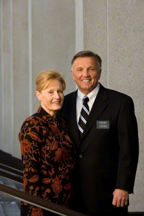 A portrait of a senior missionary couple, with the sister in an orange and black floral blouse and her husband in a black suit.
