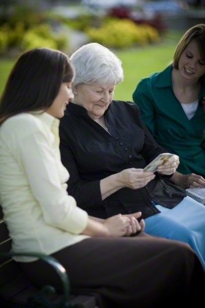 An elderly woman in a black blouse and blue skirt sitting between two sister missionaries and holding a pass-along card with a picture of Christ.