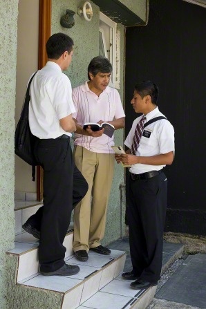 A man holding an open Book of Mormon and standing on his doorstep while talking to two elder missionaries in New Mexico.