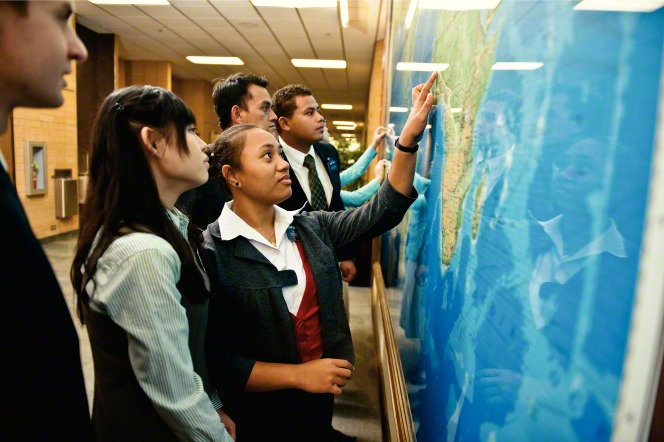 Elder and sister missionaries standing by a wall in the Missionary Training Center, pointing at a large map of the world.