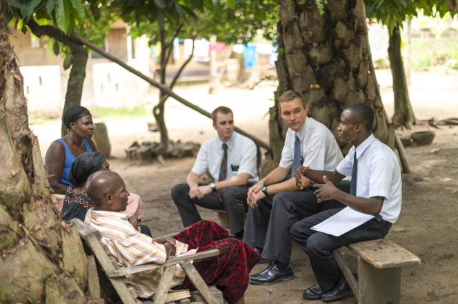 Three elder missionaries in Africa sit outside on wooden benches across from three people and teach them the gospel.