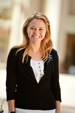 A portrait of a sister missionary with long blond hair, a white shirt, and a black cardigan, standing and smiling.
