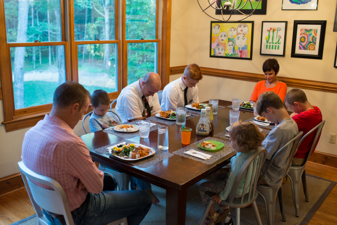 A father, mother, three sons, and a daughter sitting at a table and praying with two elder missionaries before eating their meal.