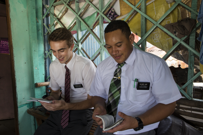 Two elder missionaries in white shirts sit inside a home and read aloud.