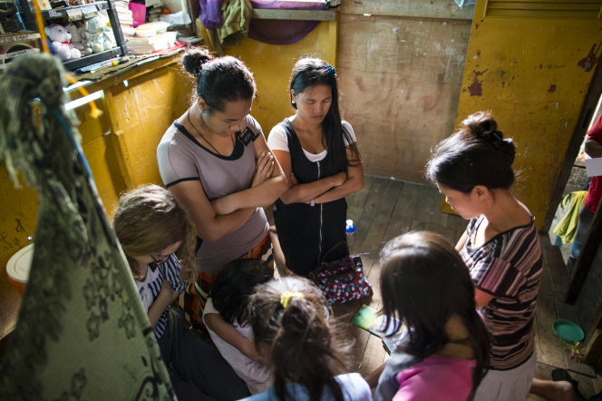 Three sister missionaries kneeling and praying on a wooden floor in a yellow tin home with a family in the Philippines.