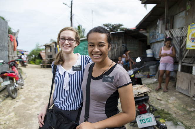 A sister missionary with blond hair and glasses standing next to her companion, who has brown hair, in a street in the Philippines.