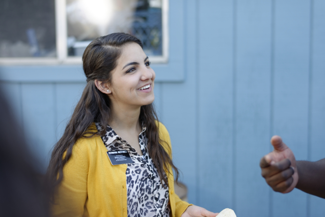 A sister missionary with brown hair and a yellow cardigan smiles as somebody talks to her outside.