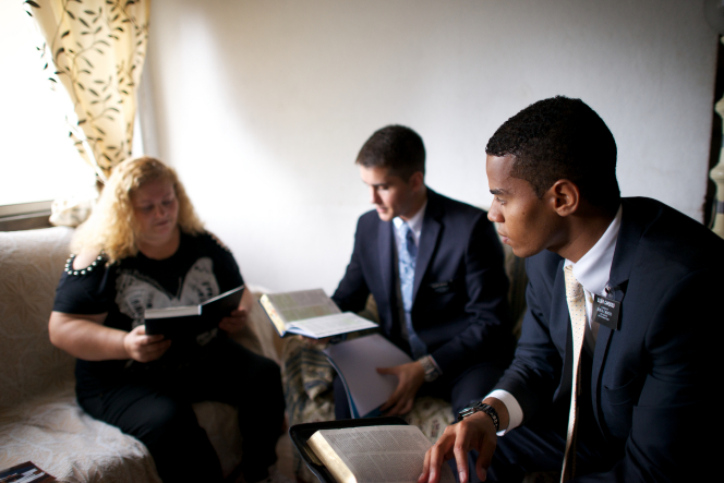 A woman sitting on a couch next to a window in her home, reading scriptures with two elder missionaries.
