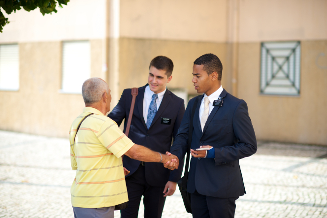 An elderly man in a yellow shirt shaking hands with two elder missionaries while standing in a street in Portugal.