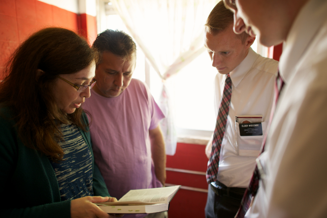 A couple standing and reading from the scriptures in their home, with two elder missionaries standing across from them.