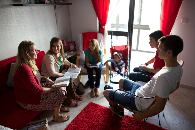 Two sister missionaries in Portugal sitting on a couch and using the scriptures to teach a mother, two sons, and a daughter in their home.