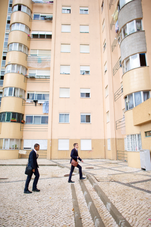 Two elder missionaries in suits, carrying shoulder bags, walk beside tall, cream-colored buildings in Portugal.