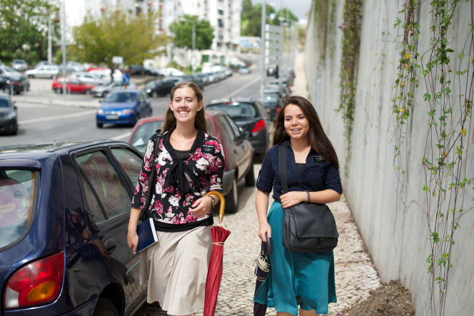 Two sister missionaries smile while carrying closed umbrellas and walking down a sidewalk next to a cement wall in Portugal.