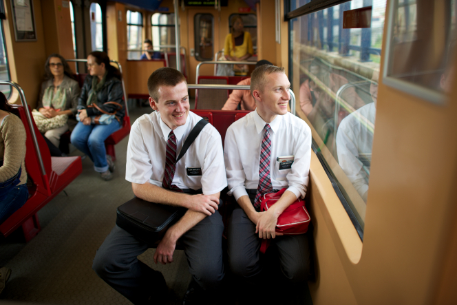 Two elder missionaries in Portugal sit on a train together and smile while looking out a window.