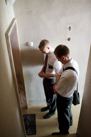 Two elder missionaries wearing white shirts, black pants, ties, and shoulder bags stand outside a closed door and pray before knocking.