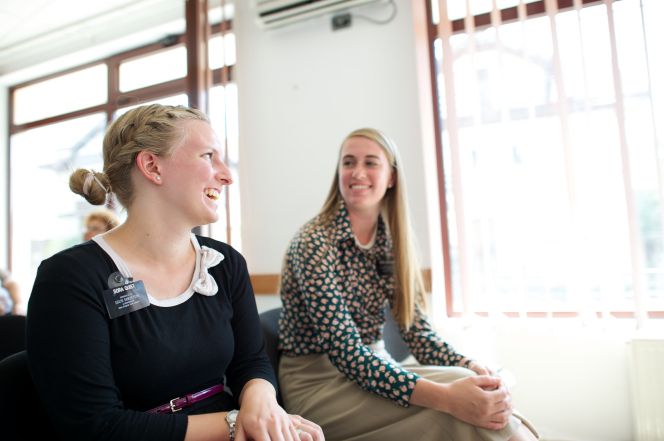 Sister missionaries from Romania look at each other and laugh while sitting next to a large window in a Church meeting.