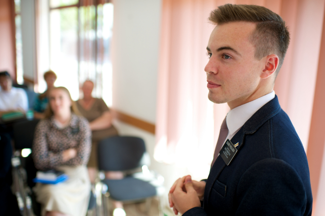 An elder missionary in Romania standing with clasped hands, teaching Sunday School in a classroom of adults.