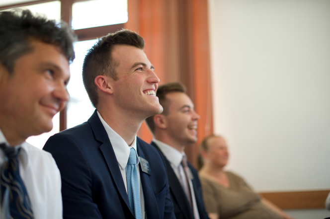 Two elder missionaries smiling while sitting between a man and woman in a Church meeting in Romania.