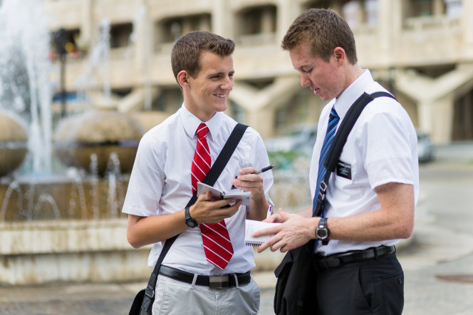 Two elder missionaries with white shirts, ties, and shoulder bags, standing in a street and writing in small white planners.
