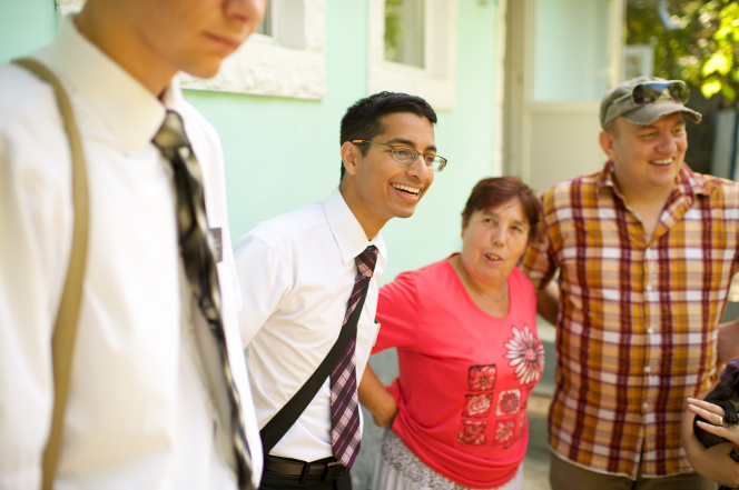 Two elder missionaries from Romania standing outside beside a woman with short hair and a man with a hat and a plaid shirt.
