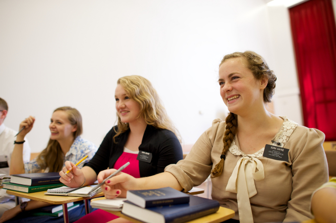 Three sisters in Romania laugh and sit at desks with scriptures, books, and pens in a classroom.