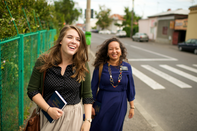 A sister missionary in a blue dress holds a Book of Mormon while walking down a street in Romania behind her companion in a polka-dot shirt.