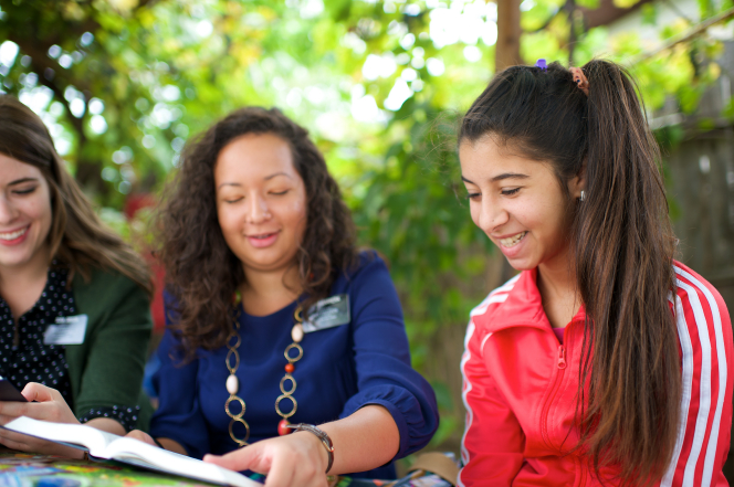 Two sister missionaries in Romania sit outside at a table while holding an open book and teaching a young woman wearing a red jacket.