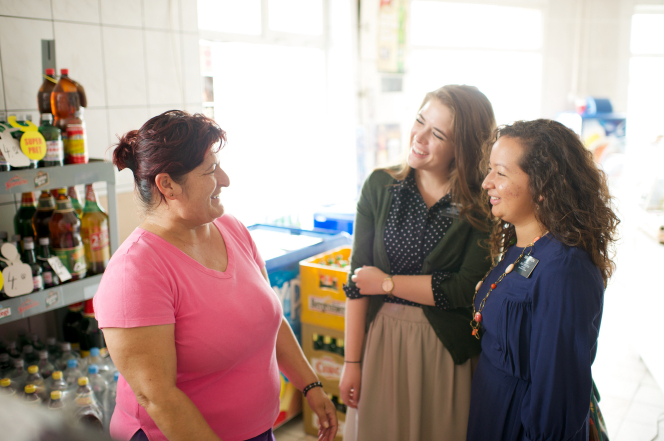 Two sister missionaries from Romania standing in a store, smiling and talking to a woman in a pink shirt.