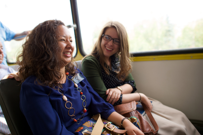 A sister missionary laughs with her companion sitting beside her as they ride on public transportation in Romania.