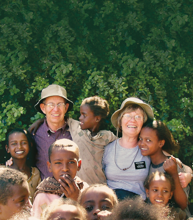 A senior missionary couple wearing hats, standing outside and hugging a group of children from Ethiopia