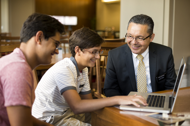 Two young men with glasses sit at a table and do family history on a laptop, with a senior elder missionary sitting beside them.